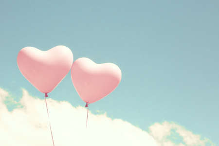 coral: Two pink heart shaped balloons in turquoise sky