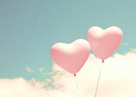 retro wallpaper: Two pink heart shaped balloons over turquoise sky