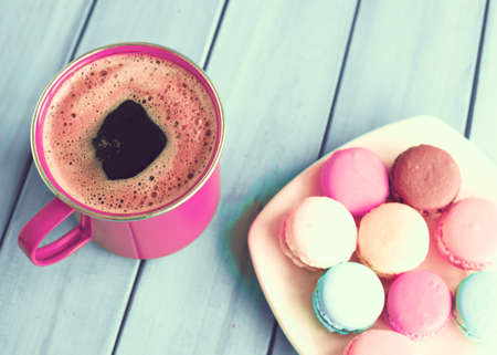 Macaroons and coffee cup over wood
