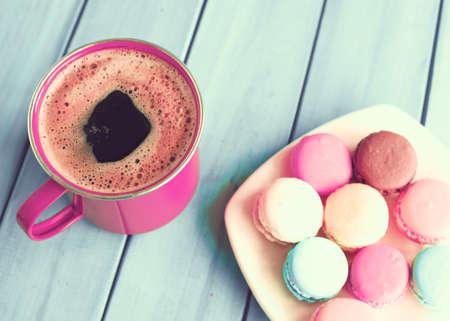menta: Macarrones y taza de café sobre la madera