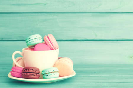 color background: Colorful macaroons in a cup over turquoise wood Stock Photo
