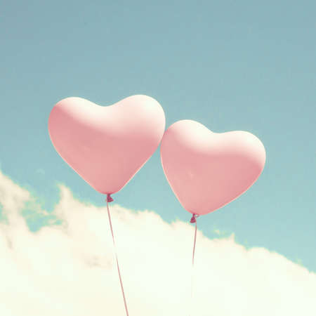 Two heart shaped balloons in turquoise sky