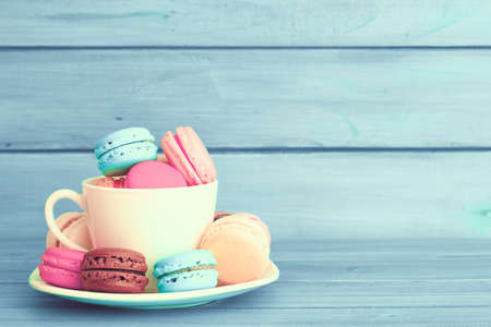 Colorful macaroons in a cup over turquoise wood Stock Photo