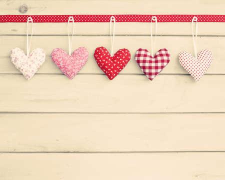 fondos azules: corazones de peluche sobre la madera que cuelgan de una cinta roja