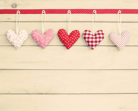 romantic love: Stuffed hearts over wood hanging from a red ribbon