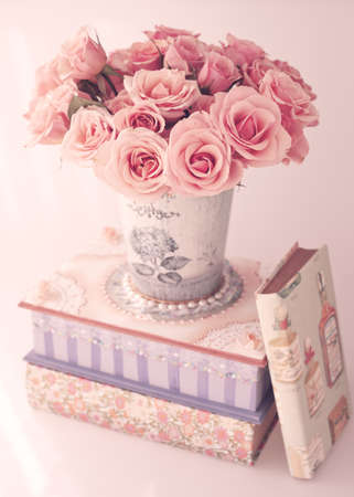 peony: Vintage roses in a vase over a girly box and books Stock Photo