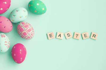 menta: Vintage huevos de Pascua en colores pastel sobre el fondo de la menta con el mensaje de Pascua en azulejos Foto de archivo