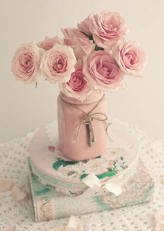 skeleton key: Roses in a pink vase with skeleton key over books Stock Photo