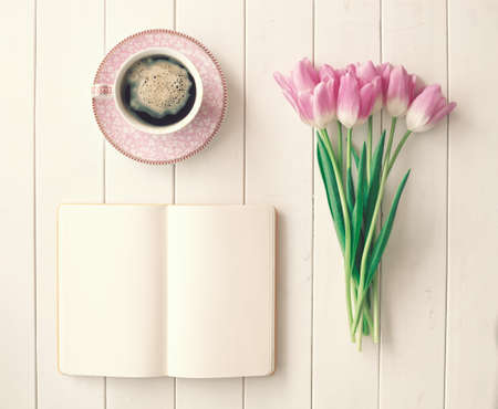 Pink tulips, coffee cup and notebook over white wood Stockfoto