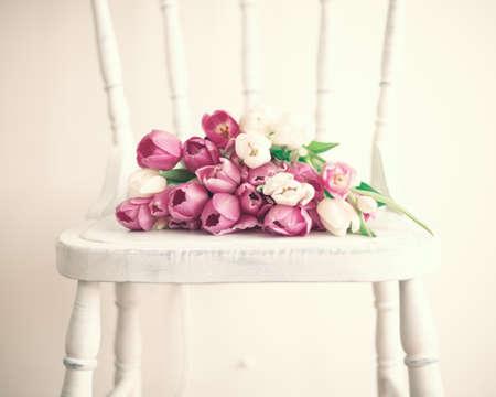 casa de campo: tulipanes rosados ??y blancos sobre una silla de madera de época Foto de archivo