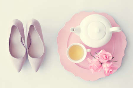 fashion art: Heel shoes, tea cup, teapot and roses flat lay Stock Photo
