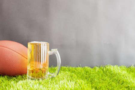 jarra de cerveza: el fútbol y la cerveza jarra de la vendimia sobre la hierba y el fondo negro Foto de archivo
