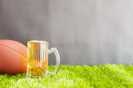 tarro cerveza: Vintage football and beer jar over grass and black background