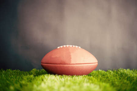field mint: Vintage football over grass and black background