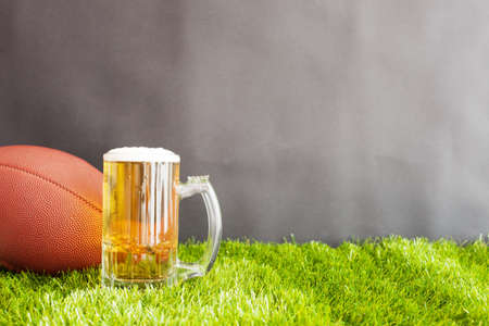 Vintage football and beer jar over grass and black background