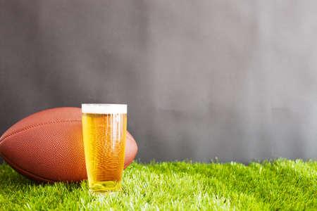 Vintage fotbal a pivní sklenice přes trávu a černé pozadí