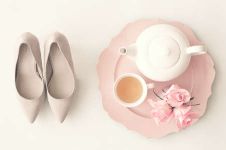 feminine background: Heel shoes, teapot, tea cup and roses Stock Photo