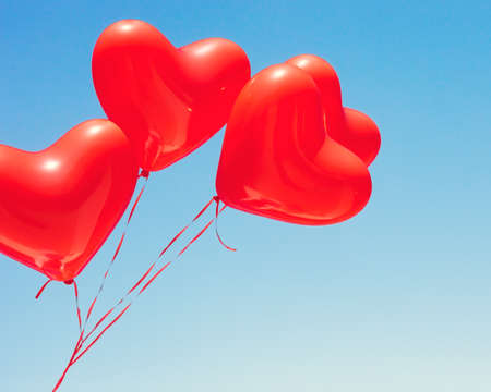 Various red heart shaped balloons in flight Stock Photo