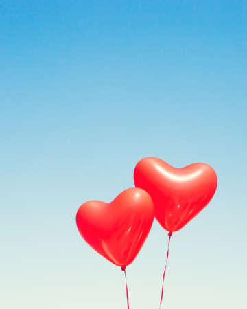 Two red heart shaped balloons in flight Stock Photo