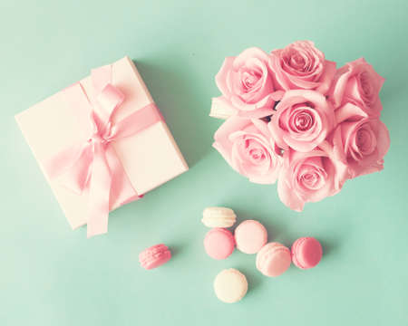 Pastel macarons and roses over mint