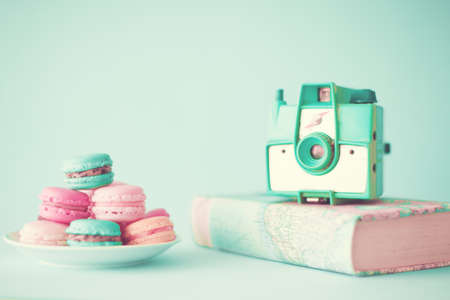 Pastel macarons and camera over book