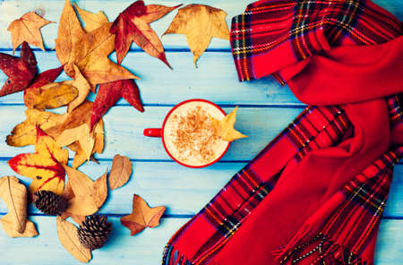 Coffee cup, autumn leafs, pine cones and scarves over turquoise wood