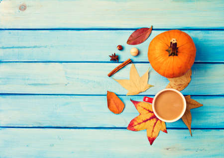 Coffee cup, autumn leafs, and spices over turquoise wood Banco de Imagens