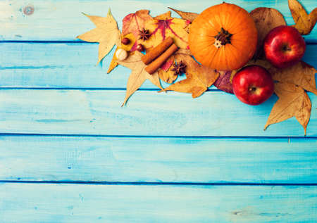 Pumpkins, apples, spices and autumn leafs over turquoise wood
