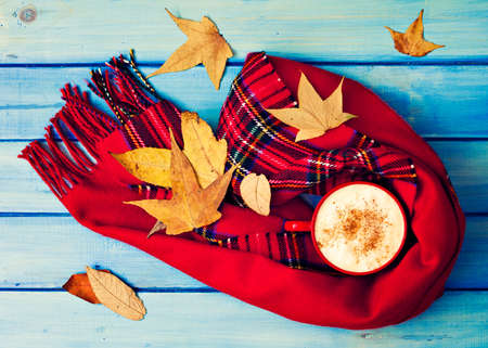 Coffee cup, scarves and autumn leafs over turquoise wood Banco de Imagens - 88065901