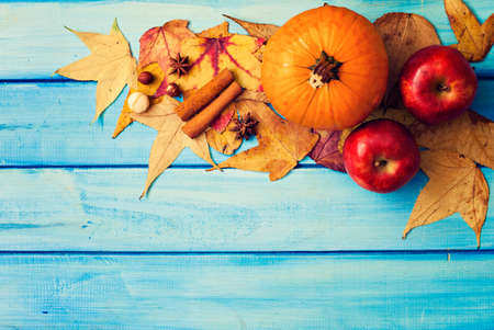 Apples, pumpkin, spices and autumn leafs over turquoise wood Banco de Imagens - 88065903