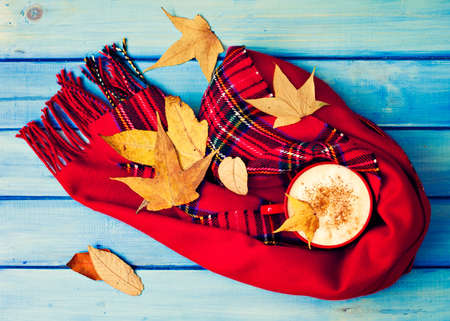 Coffee cup, scarves and autumn leafs over turquoise wood Banco de Imagens - 88065904