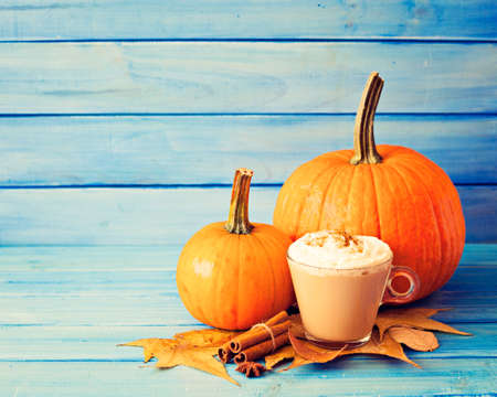 Coffee cup, pumpkin, spices and autumn leafs over turquoise wood Banco de Imagens