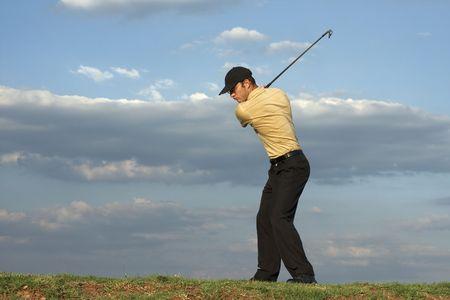 mediodía: El hombre balance�ndose un club de golf tarde despu�s de mediod�a