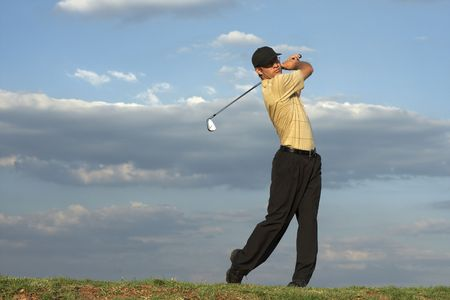 driving range: Man swinging a golf club late after noon