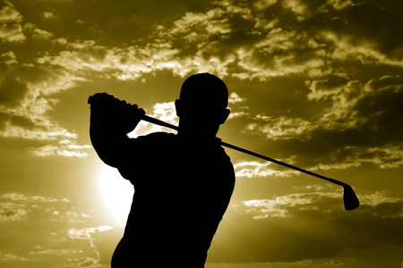 stance: Man swinging a golf club late after noon