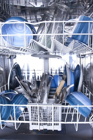 Dishwasher with knives forks and blue plates photo