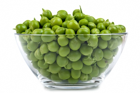 The glass cup is filled by peas on a white background