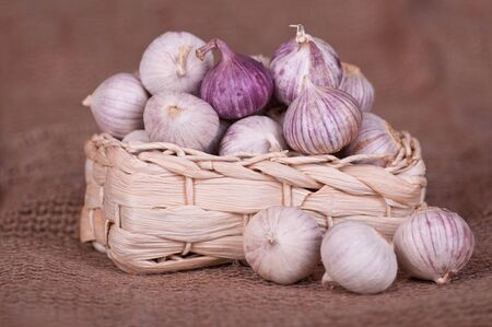 Garlic in a basket  against a sacking