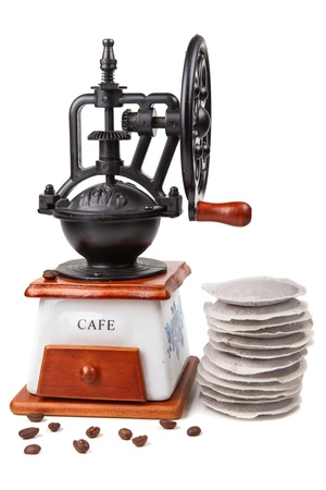 Old coffee grinder  on the white background with coffee pods Stock Photo - 17439622