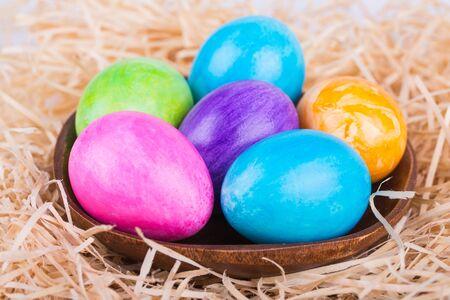 wood shavings: Colorful painted easter eggs in wood shavings