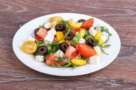 Healthy salad with fresh vegetables on wooden background