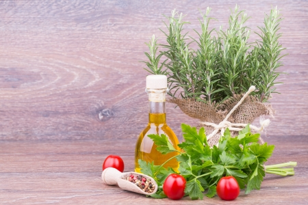 Fresh rosemary, parsley with oil on wooden  background photo