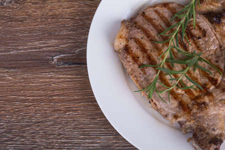 Grilled  steak with rosemary on wooden background photo