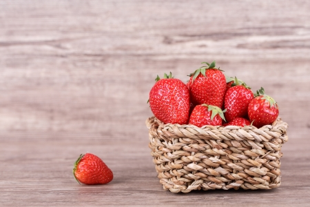 fresh strawberries in a basket on a wooden background photo