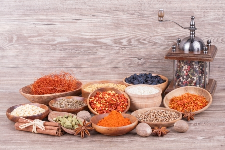 Different  spices in  wooden bowl on wooden background photo