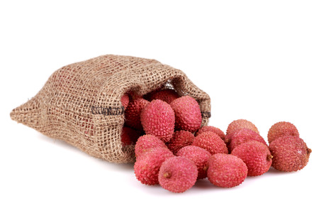 Fresh, ripe, red lychee in bag on white background