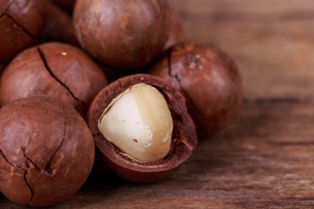 brown macadamia nuts seed on wooden background Stock Photo
