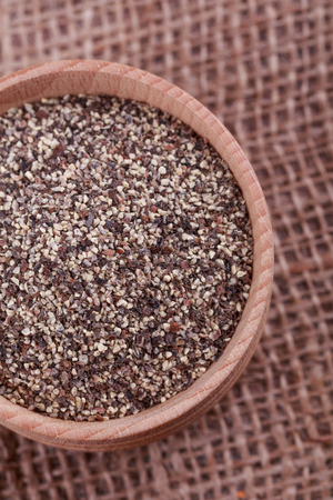 pounder: Pepper in wooden cup  on  sack cloth
