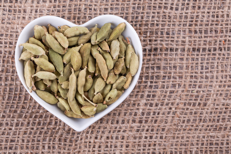 Cardamom in  cup in the shape of heart on sack  cloth