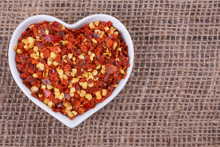 pepper flakes: chilli in  cup in the shape of heart on sack  cloth